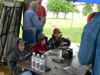 Huddling against the wind at the fly tying booth at the Outdoor Adventure Event